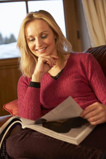Middle Aged Woman Reading Magazine On Sofa
